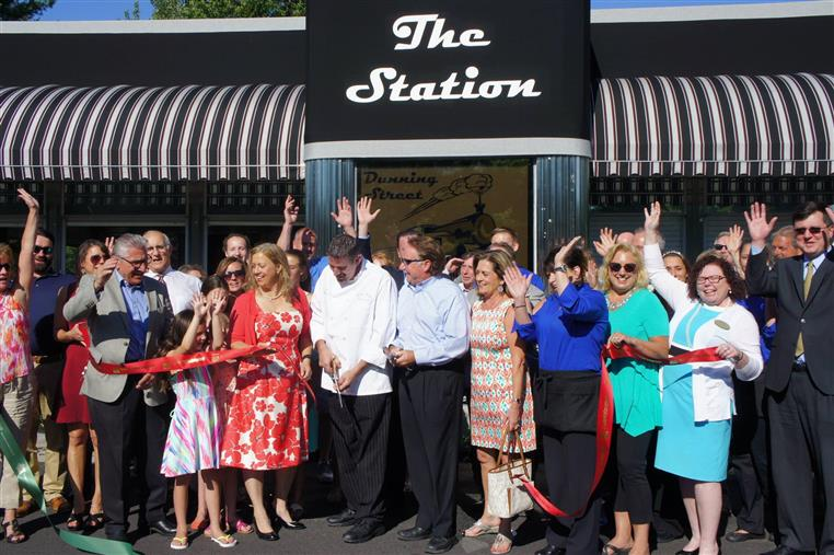 Cutting the ribbon at the grand opening. People gathered in front of the restaurant entrance celebrating