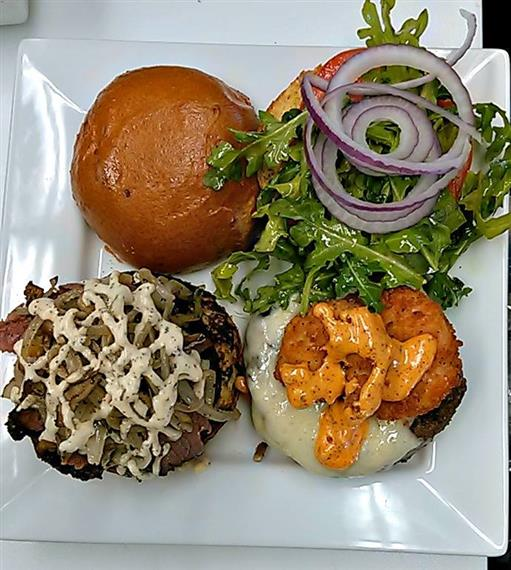 Burger patty topped with sauteed mushrooms and mayo, onion rings covered with melted cheese, mixed greens and tomato with red onions.
