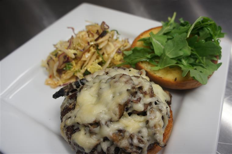 Cheese burger served open faced with sauteed mushrooms and melted cheese on one side and coriander leaves on the other side. Served in a plate with a side of slaw