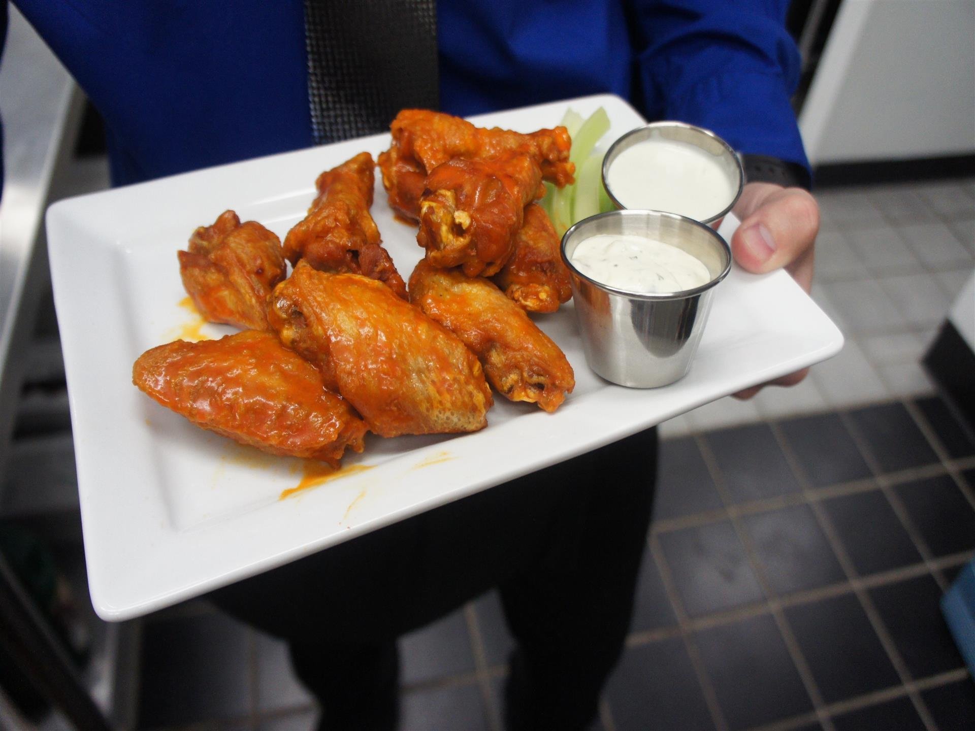 Buffalo wings with ranch and celery on white dish being held by server