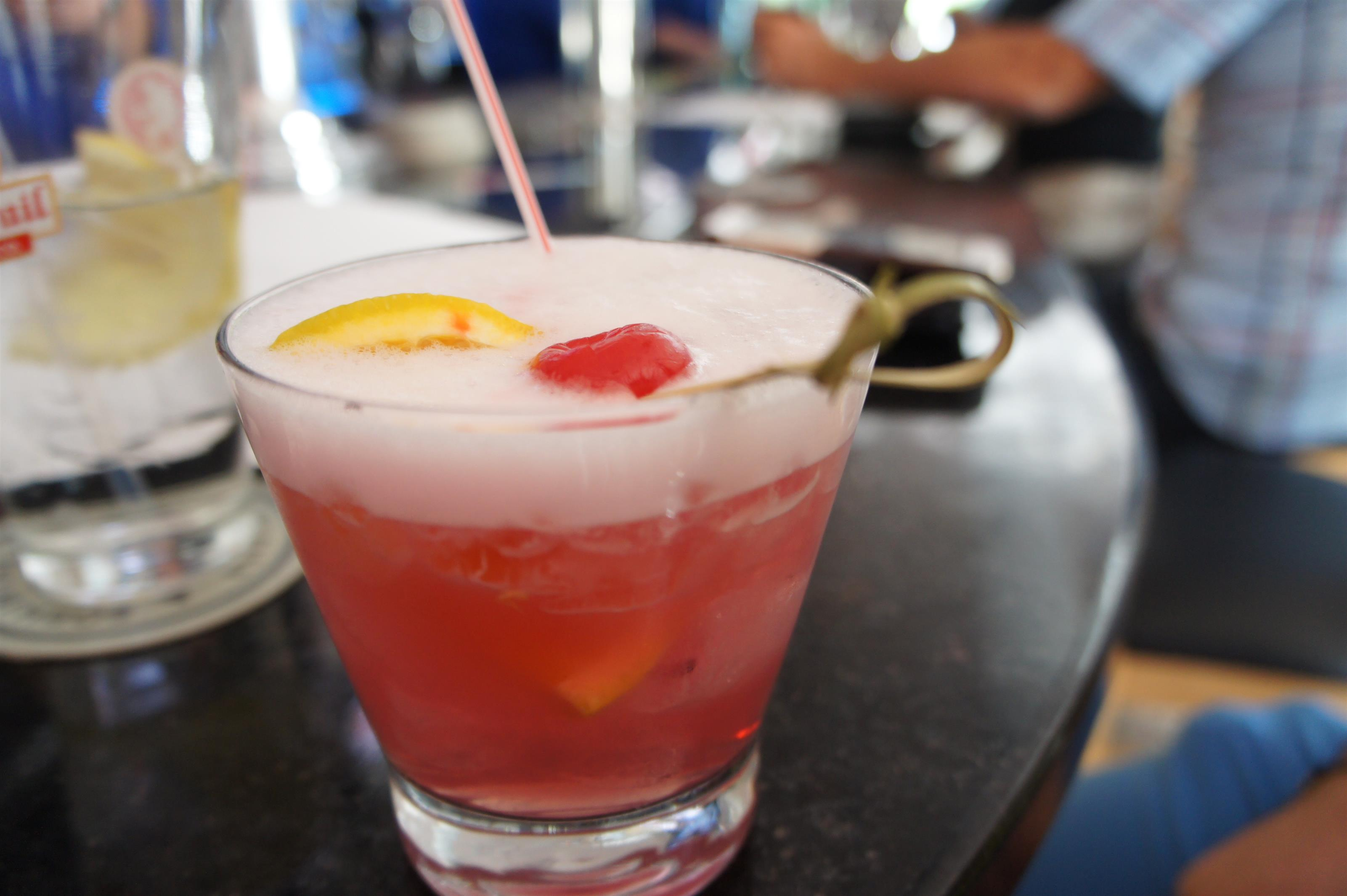 Pink cocktail drink garnished with a cherry and a lemon wedge
