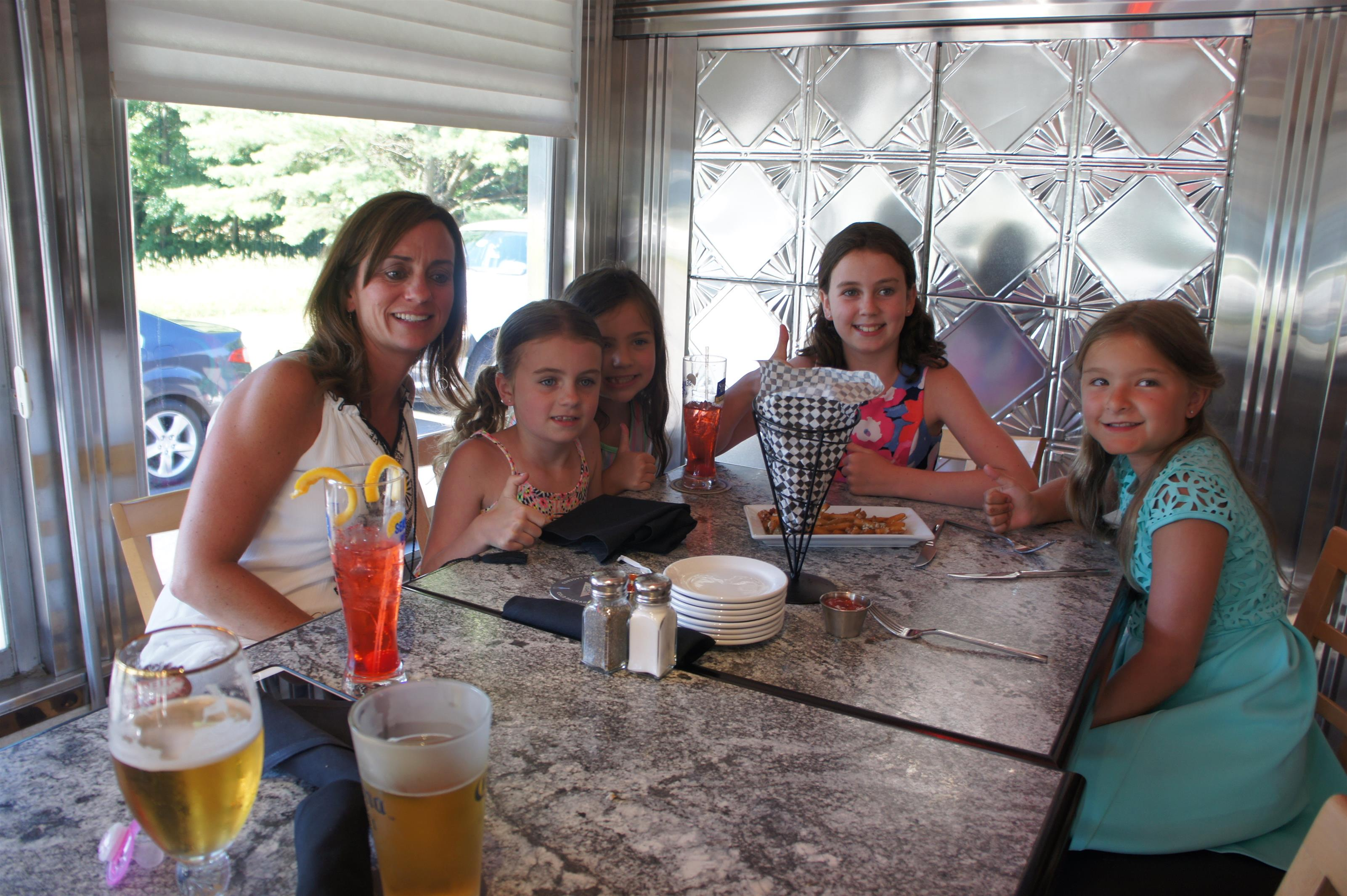 Woman with four young girls waiting at the table smiling and posing for photo