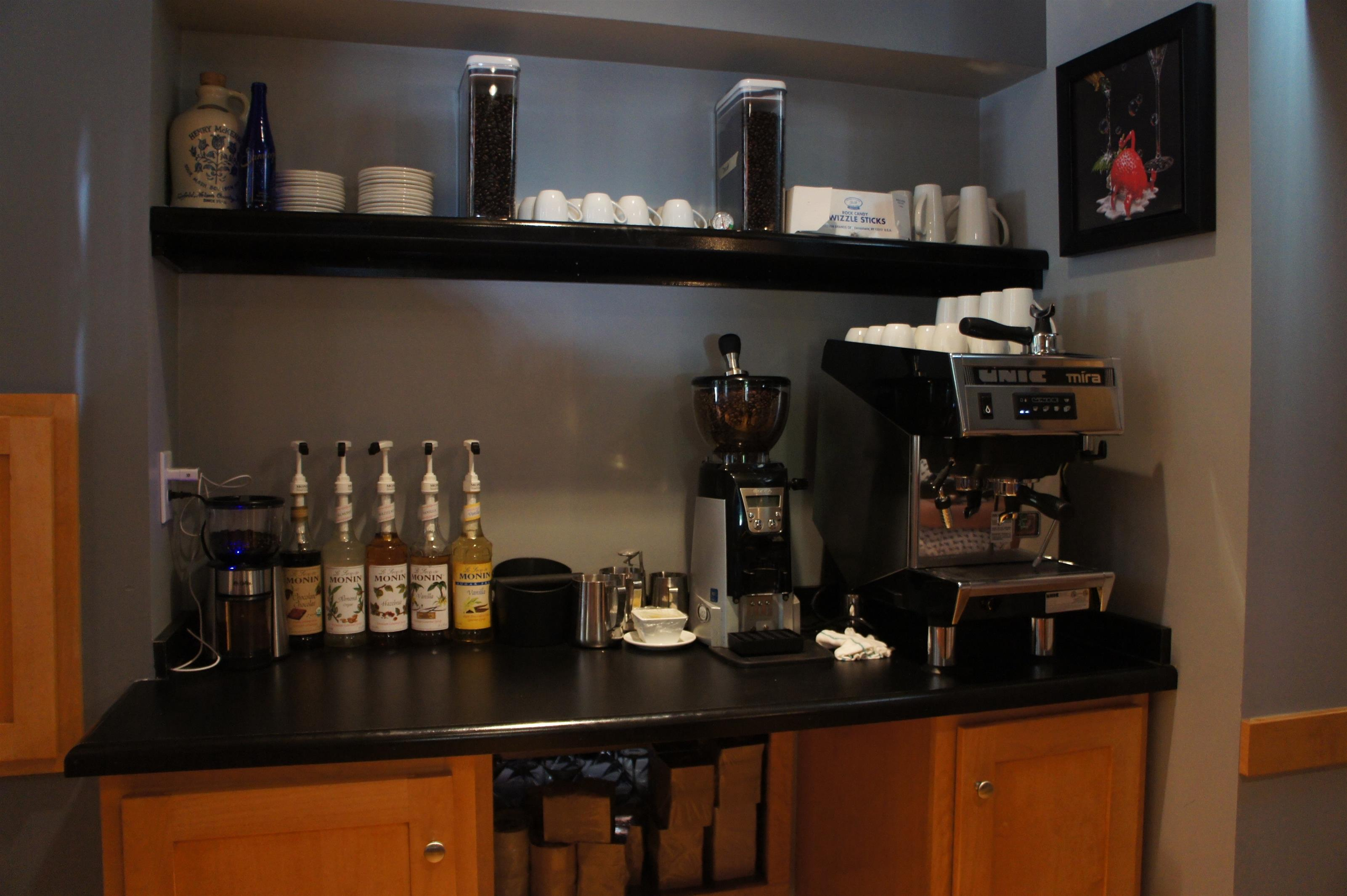 Coffee station with coffee steamer and grinder, a shelf with white coffee cups and an aaray of syrup flavors