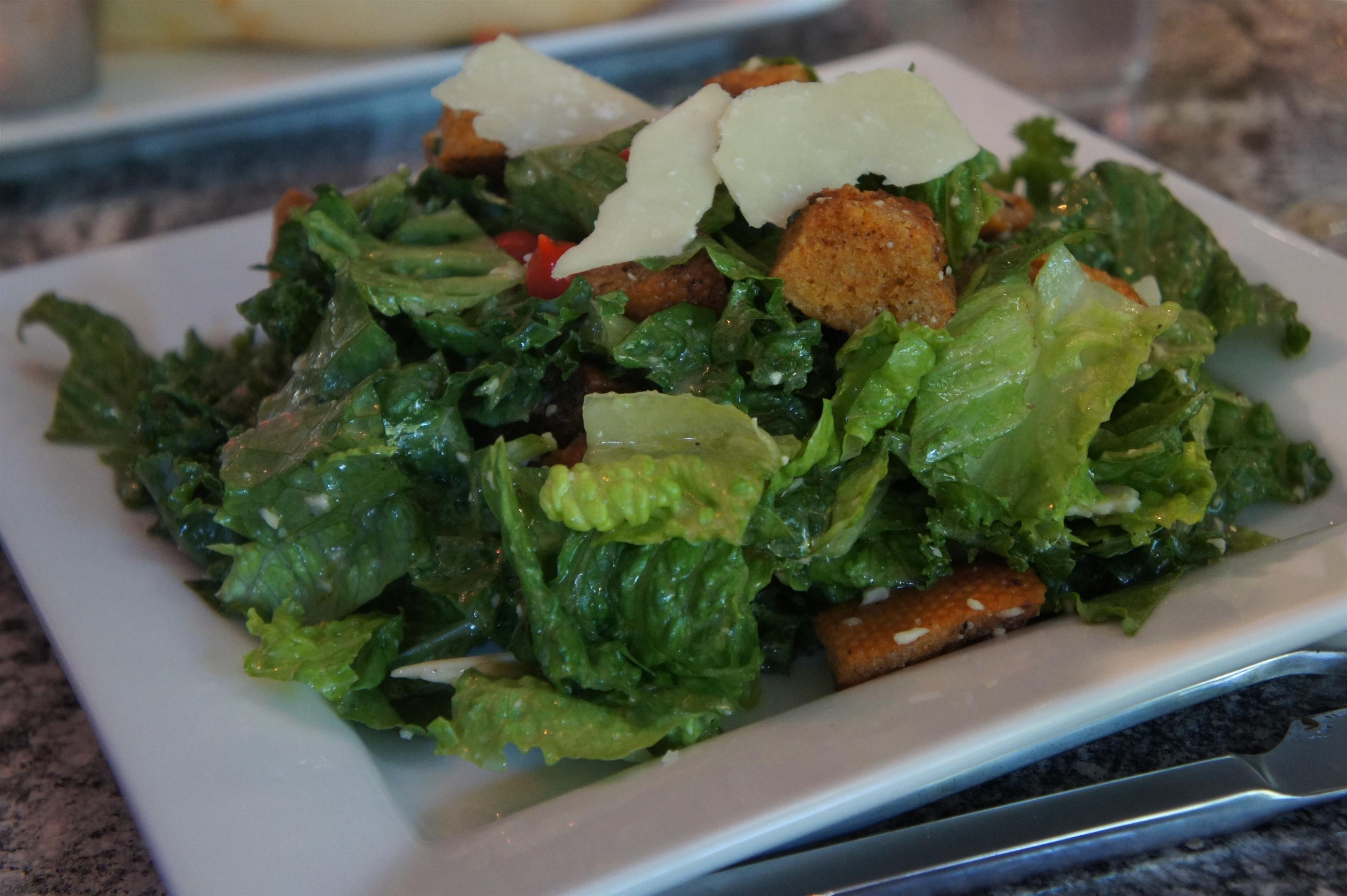 Mixed greens salad with croutons and shaved cheese tossed in dressing