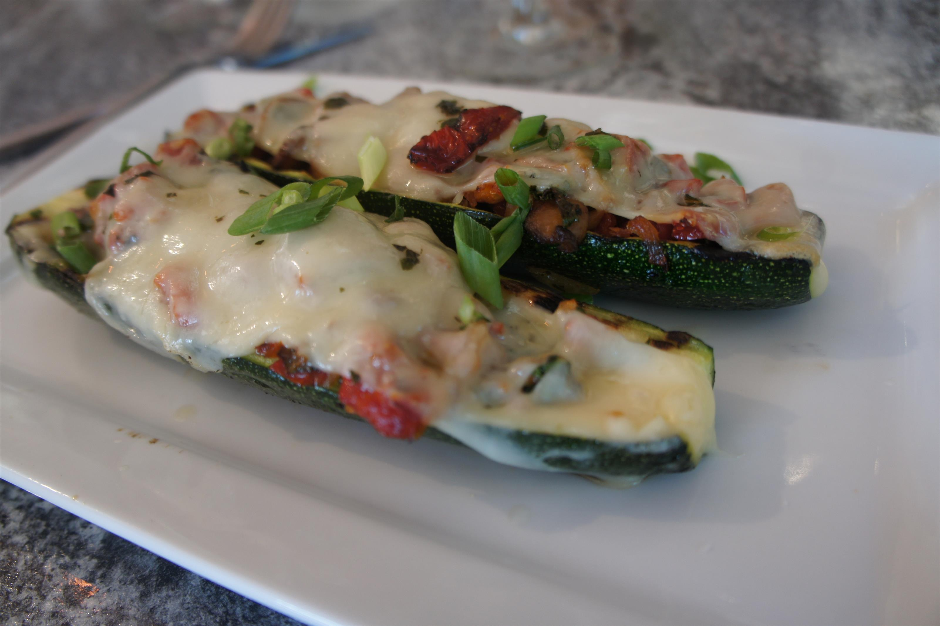 Eggplant stuffed boats with melted cheese on top served in a white platter