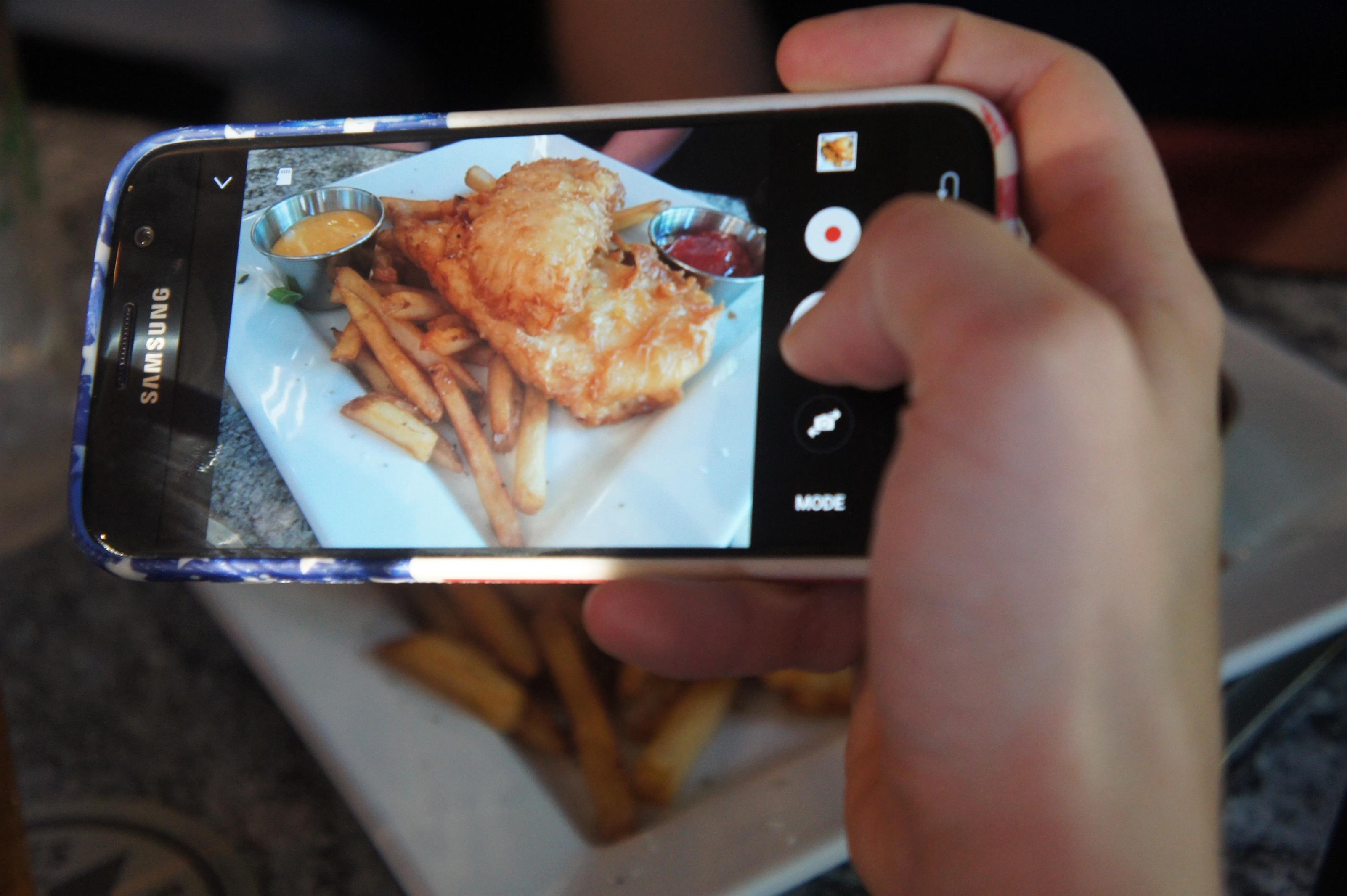 Person taking a photo of a fish and chips dish on their mobile