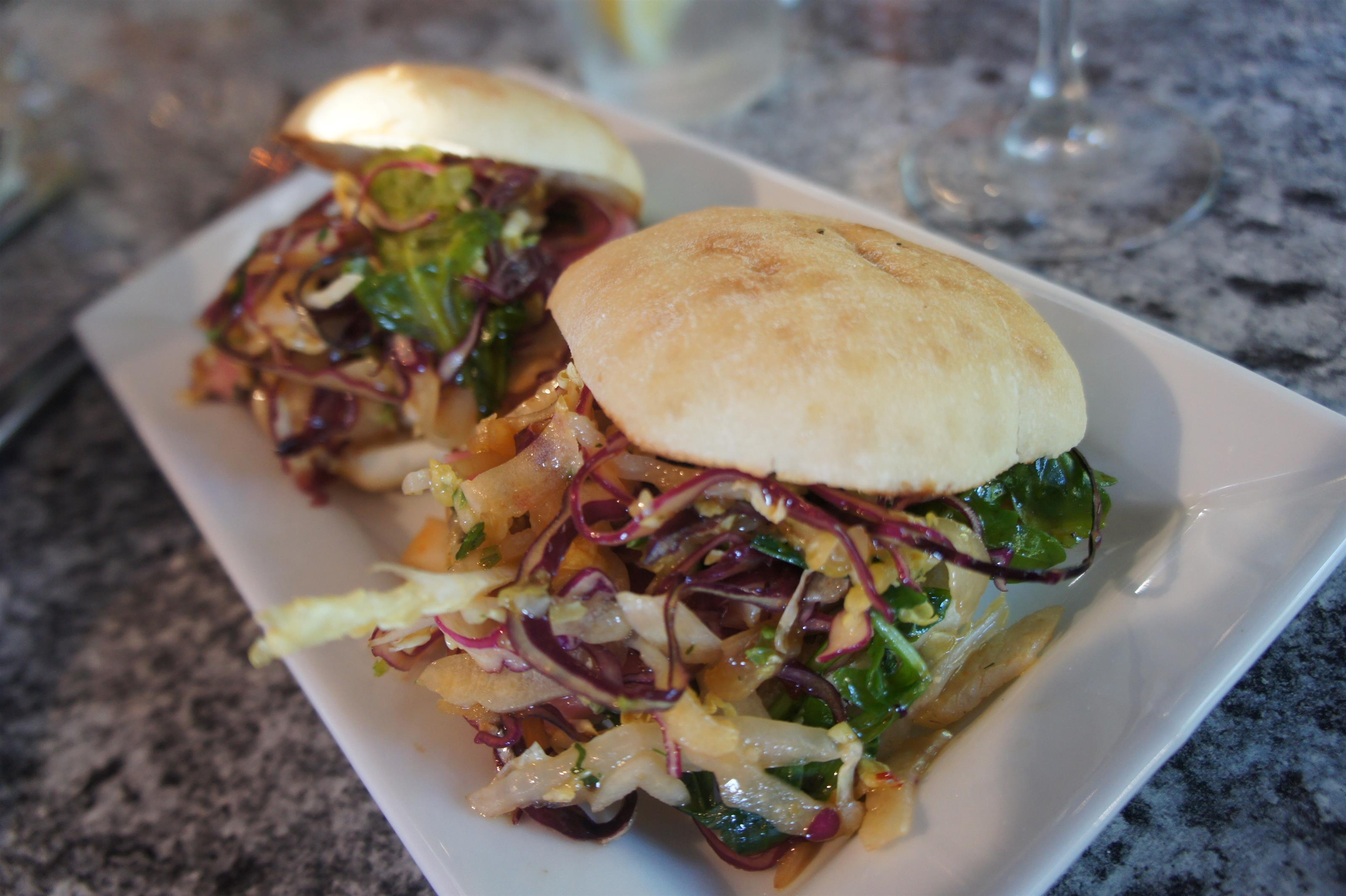 Two slider buns with mixed sauteed vegetables served in a white plate