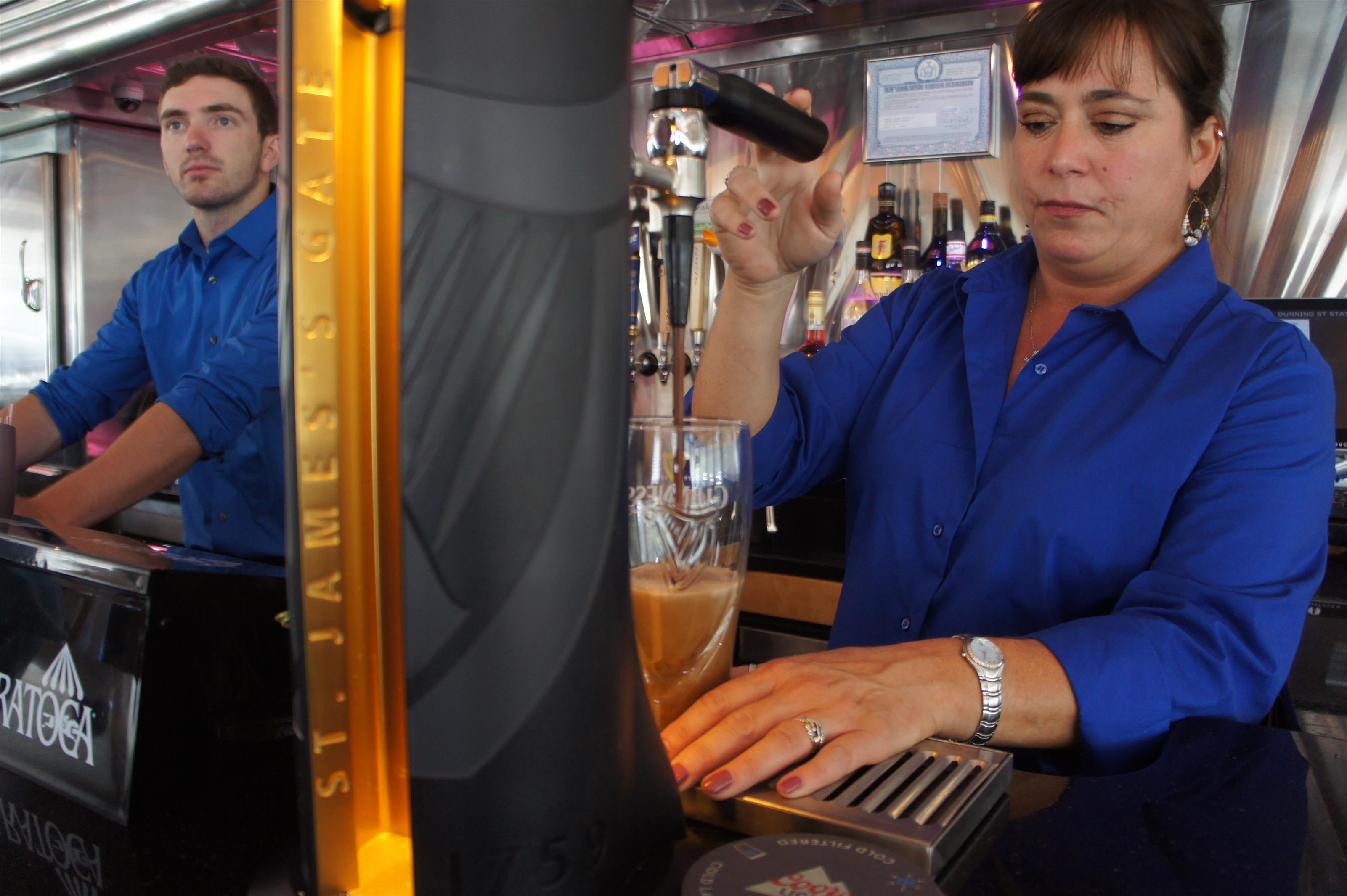 Woman and man bar tenders making drinks and pouring beer from the tap