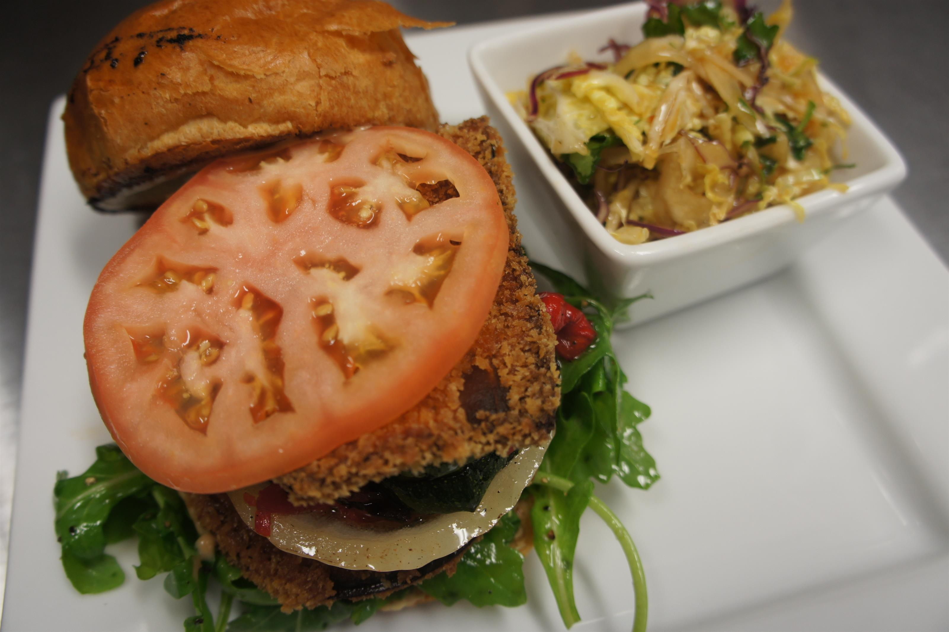 Vegetarian burger with breaded eggplant, tomato, onion, peppers and greens served open faced with a side of coleslaw