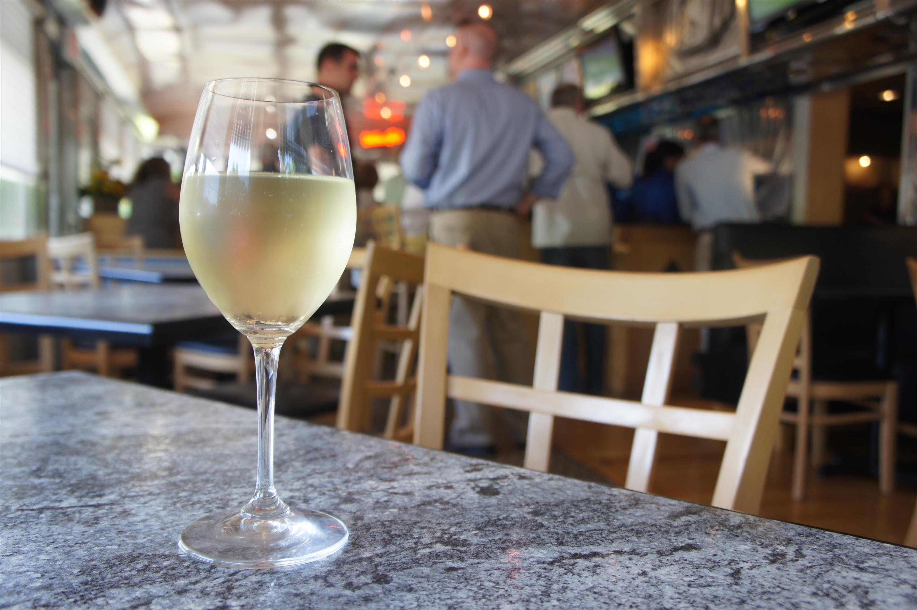 A tall glass of white wine on a table top and the restaurant hall in the background
