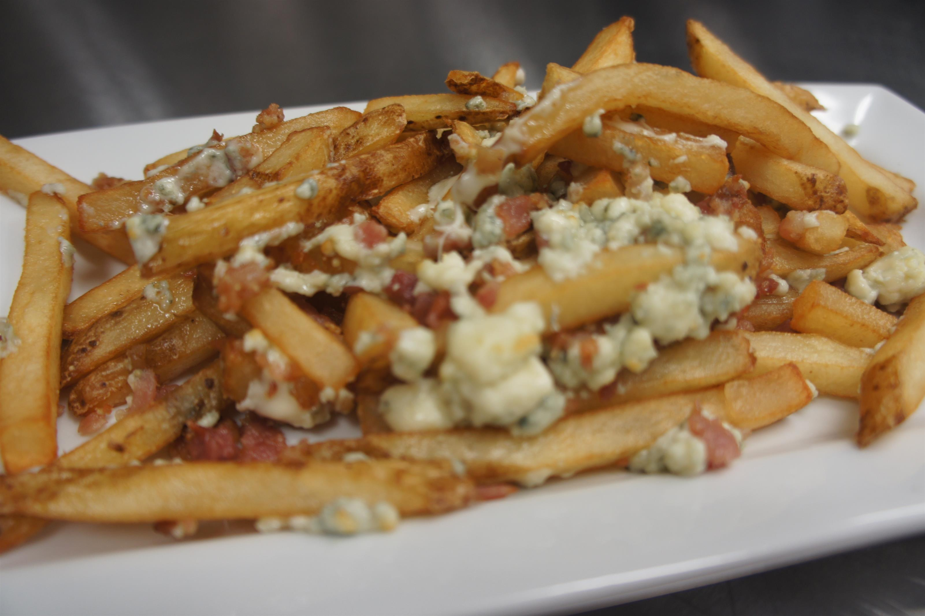 Poutine fries served with cheese curds and bacon bits