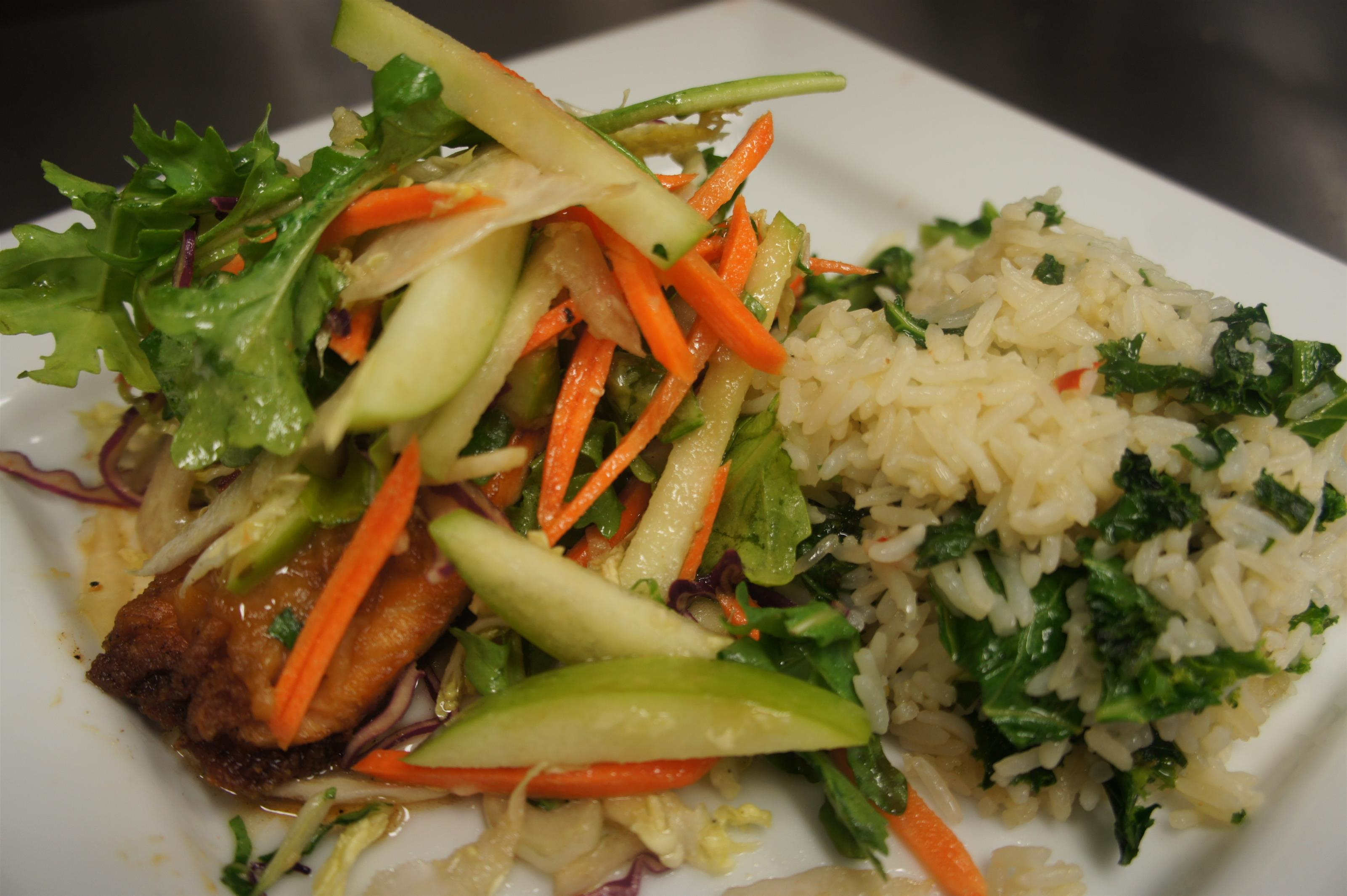 Meat dish topped with sauteed vegetables and green salad served with rice