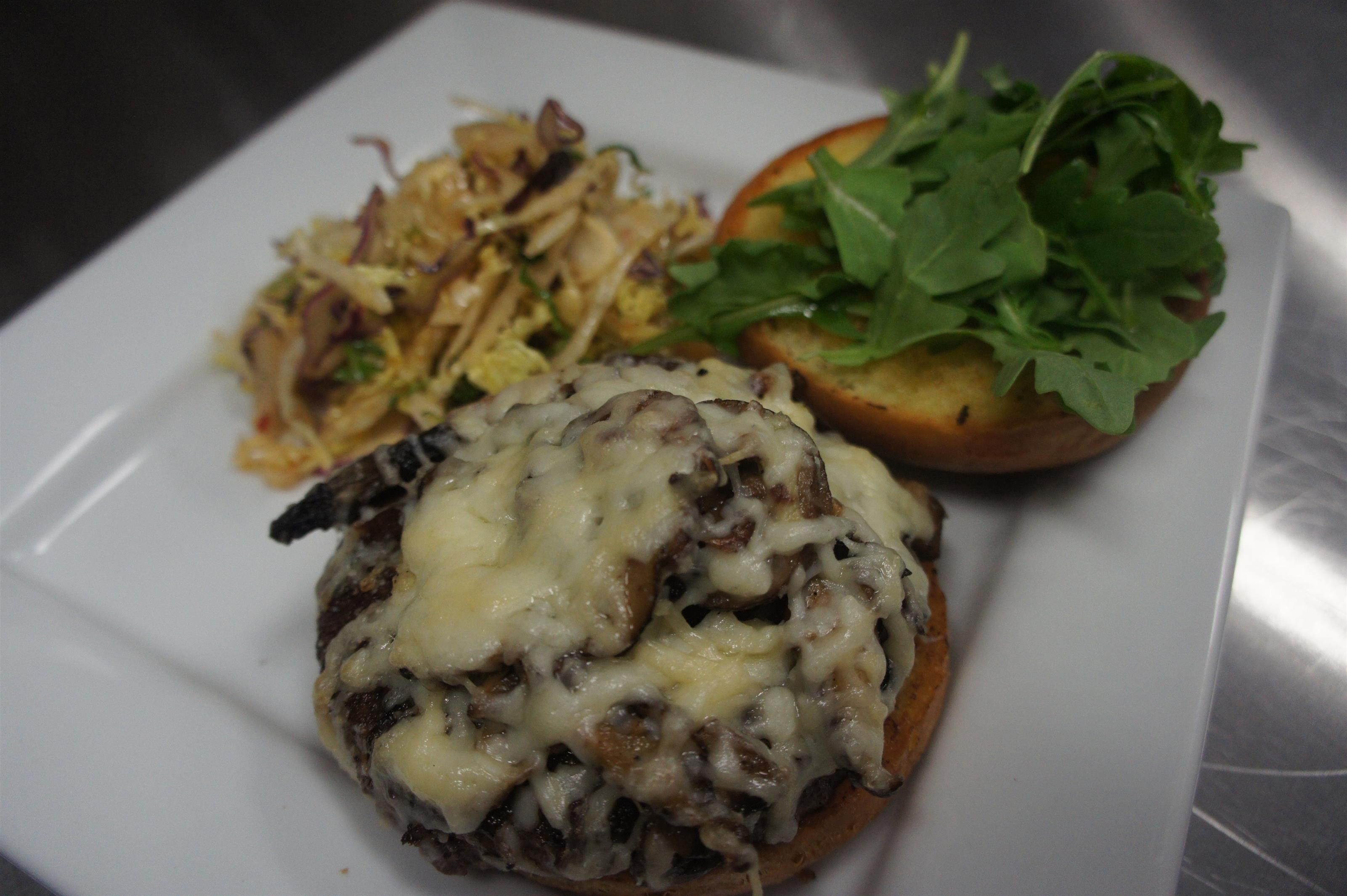 Cheese burger served open faced with sauteed mushrooms and melted cheese on one side and coriander leaves on the other side. Served in a white plate with a side of slaw