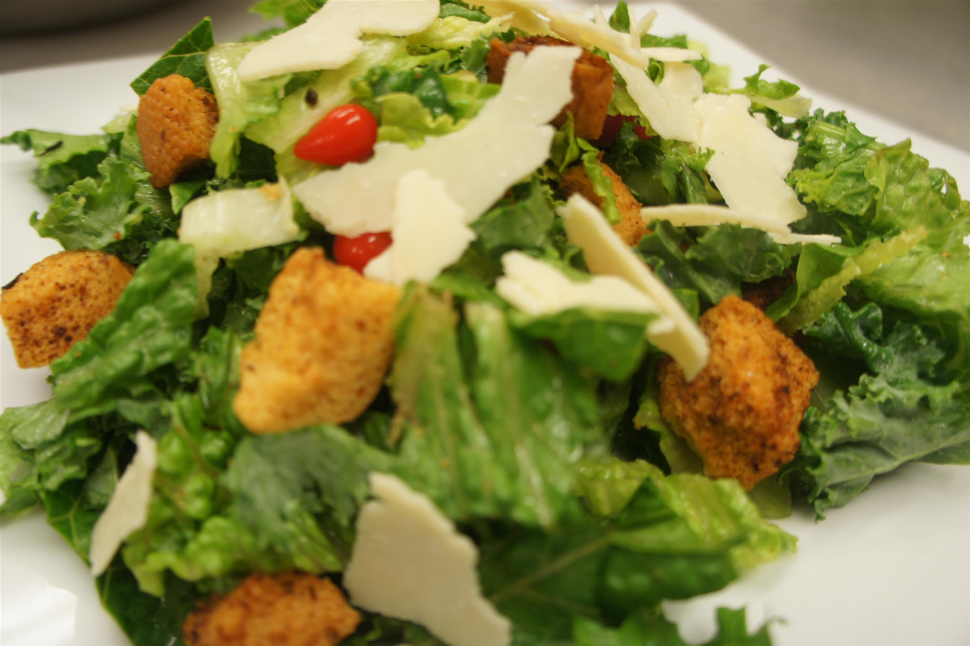 Caesar salad with crispy romaine lettuce with sweet drop peppers, shaved Parmesan and rosemary croutons