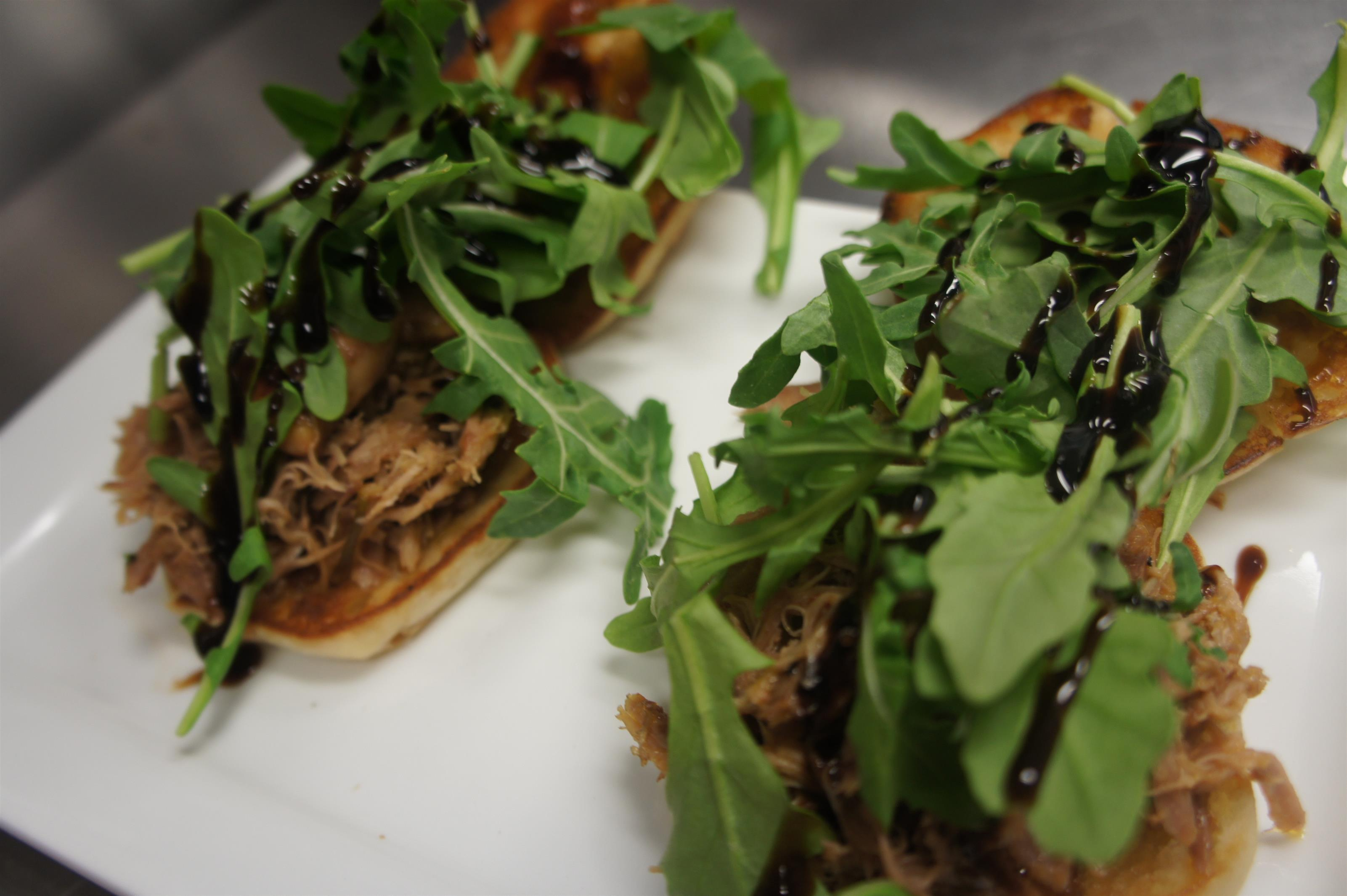 Pulled pork sliders topped with greens and drizzled with dar sauce