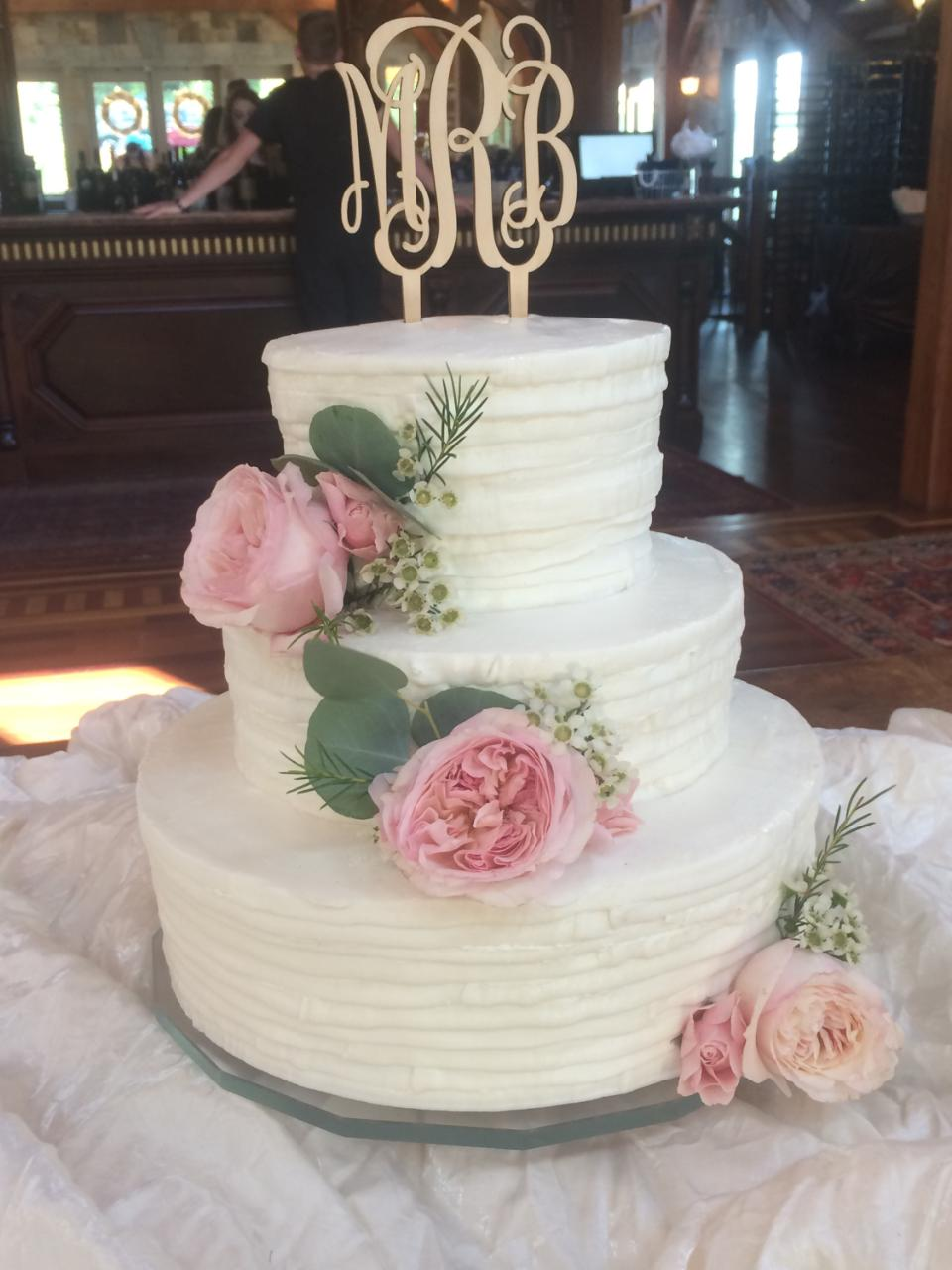 three tiered wedding cake with flowers and a monogram cake topper