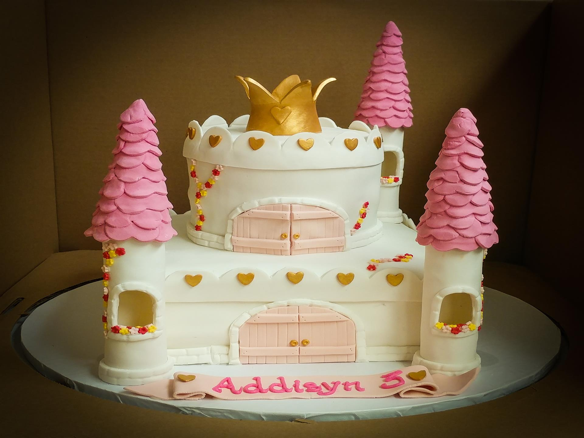 Pink and white castle cake with crown on top