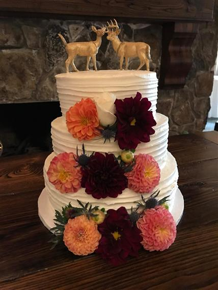 wedding cake with flowers and deer cake topper