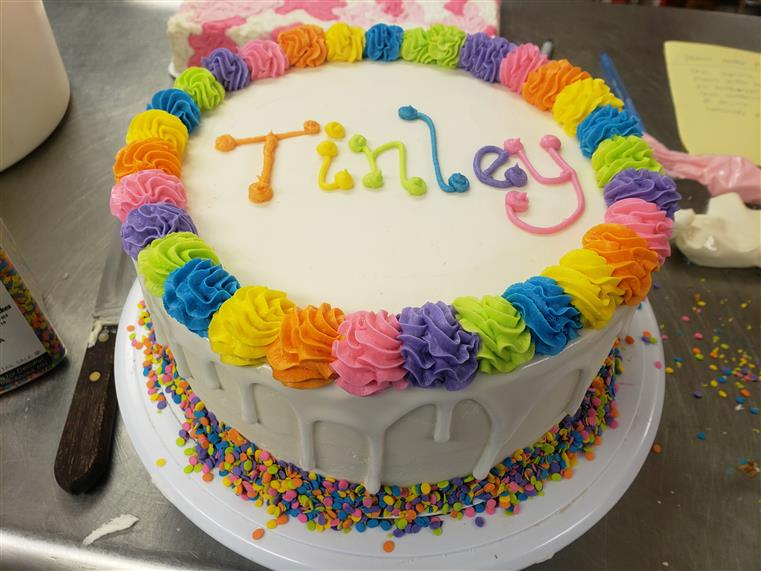 "vanila cake with sprinkles and ""Tinley"" written in icing"