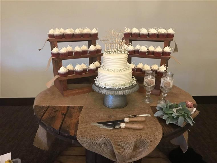 wedding cake with vanilla cupcakes and flowers on table