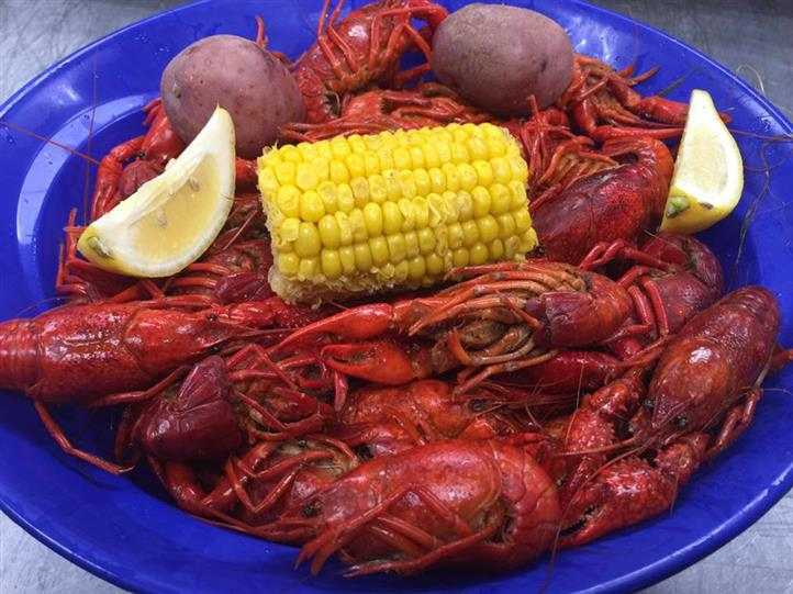 Lobsters with slices of lemon and a corn cob