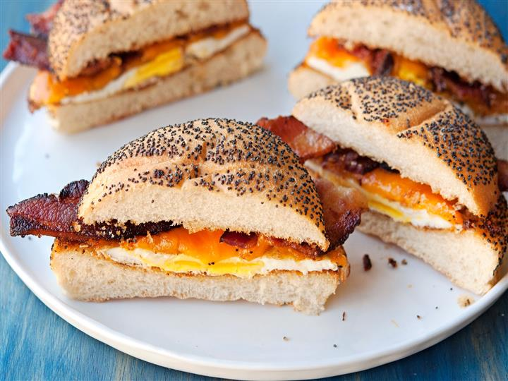 Bacon egg and cheese on a bagel with poppy seeds