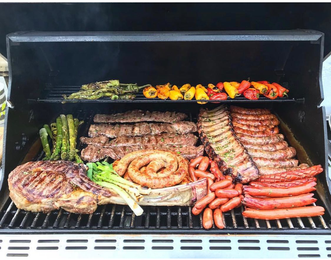 variety of sausages and ribs on a grill with vegetables