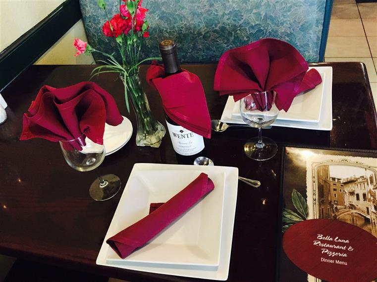 White dishes with dark red cloth napkin placesttings and bottle of wine on dining table.