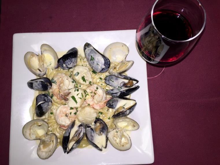 Seafood alfredo. Fresh shrimp, scallops, mussels, clams sauteed in cream sauce in white dish with glass of red wine.