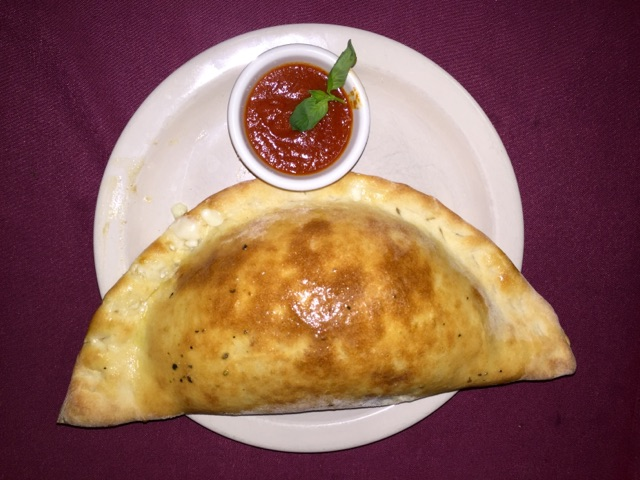 Calzone with side of marinara sauce on white dish.