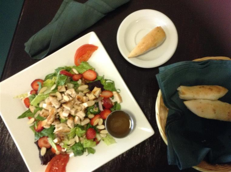 Chicken sala with tomatoes, almonds, strawberries with cup of dressing on white dish adjacent to basket of bread.