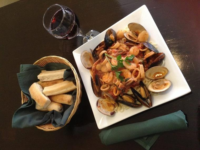 Pescatore. Calamari, mussels, scallops, clams and shrimp in marinara on white dish next to basket of bread.