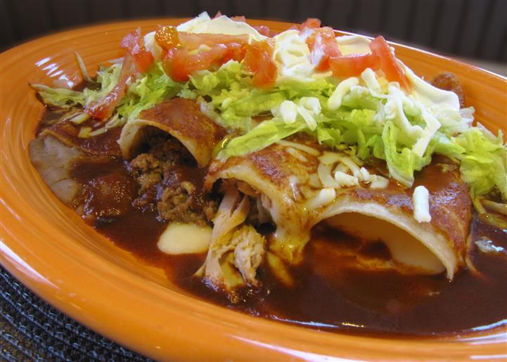 Chimichangas served win sauce and topped with shredded lettuce, tomato and cheese