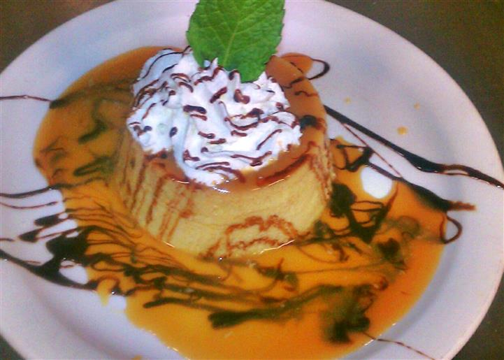 Mexican flan served with whipped cream and topped with syrup and a mint leaf