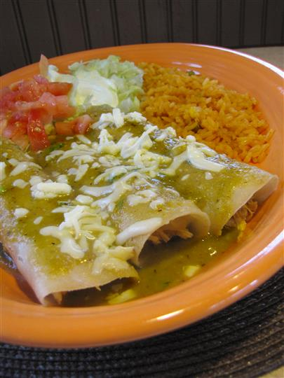 Three enchiladas served with green sauce and sides of pico de gallo, sour cream and rice