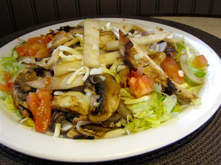 Chicken tossed salad with lettuce, tomatoes, onion and shredded cheese