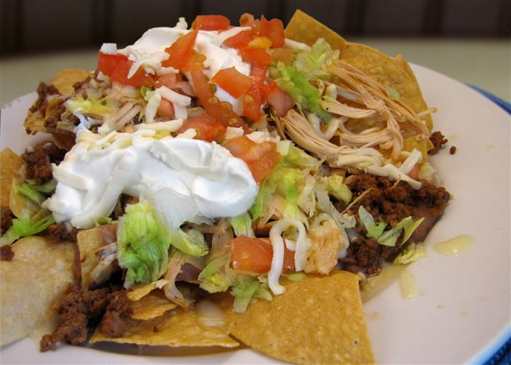 Fajita dish served with tortilla chips shredded lettuce, tomato and onion and topped with sour cream