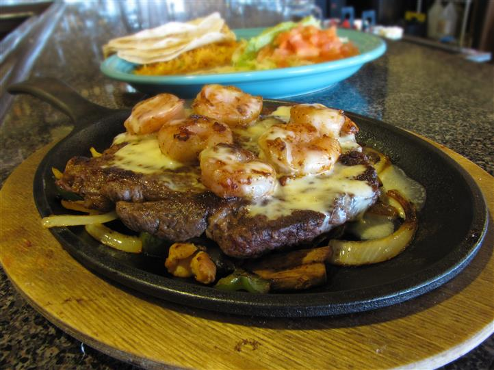 Steak and shrimp fajita dish served with a side of tortilla chips, guacamole and more salads