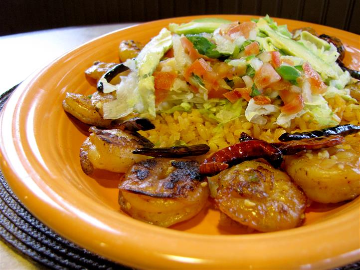 Grilled shrimp served with rice in the middle topped with shredded lettuce, tomato and onion