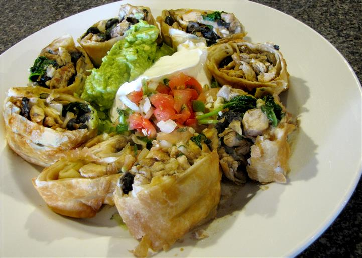 Tortilla wrapped pinwheels served with guacamole, sour cream and pico de gallo in the middle