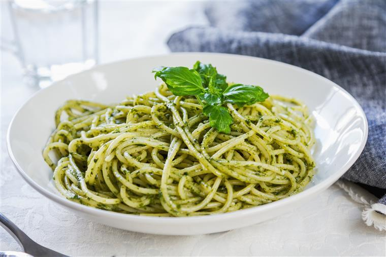 Spaghetti ith pesto in a white bowl with basil leaves on top.