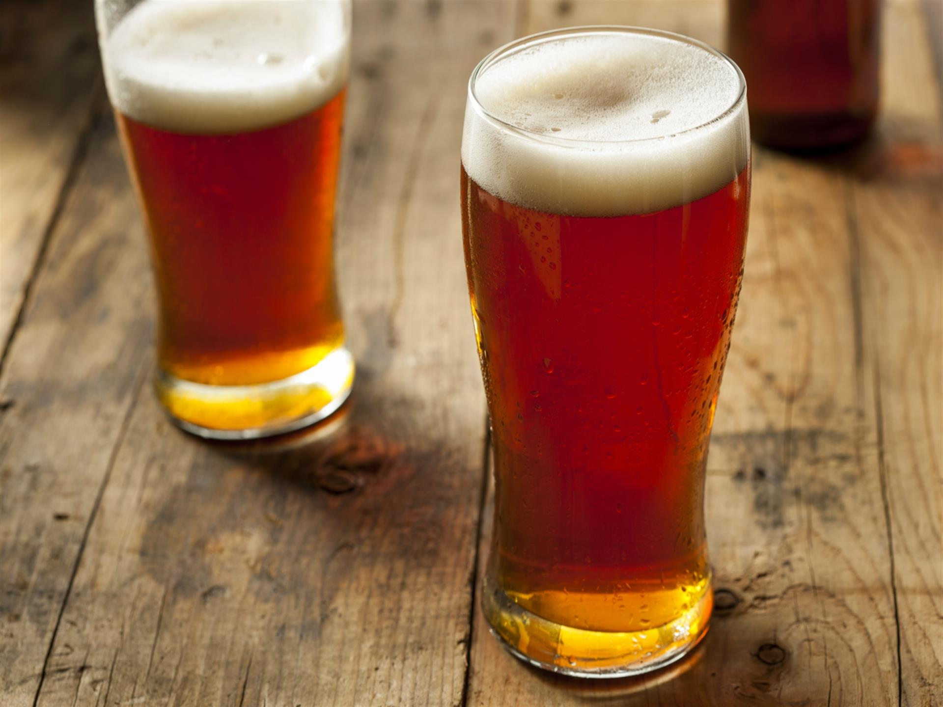 two pints of beer on a wooden table