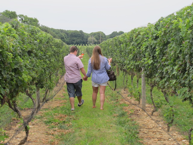 male and female walking through a wine vineyard