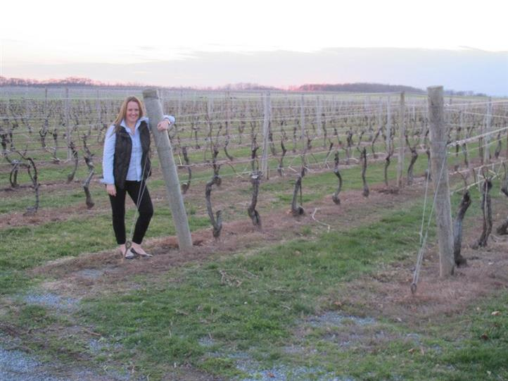 female standing in wine vineyard