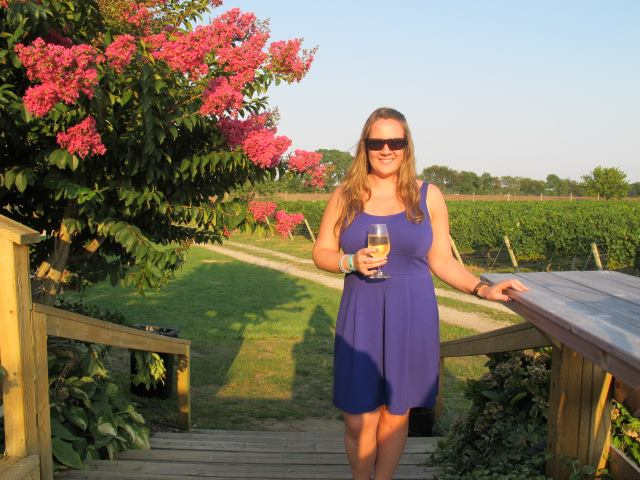 female wearing sunglasses holding glass of wine standing outside