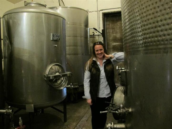 female standing next to big wine container