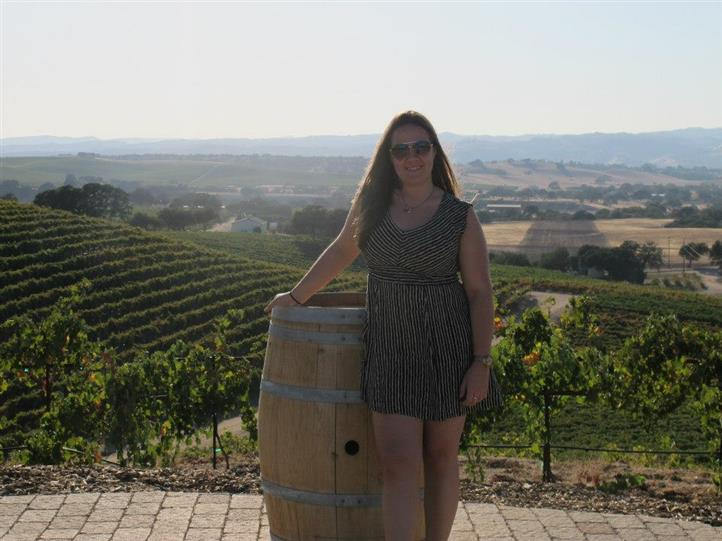 female standing next to wine barrel with wine vineyard in background