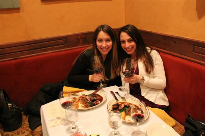 two females holding wine glasses at a table