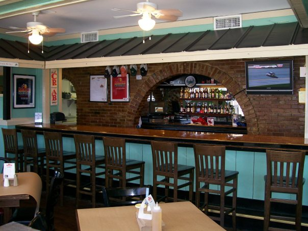 Bar counter with chairs, background is brick archway with liquor bottles on shelves.