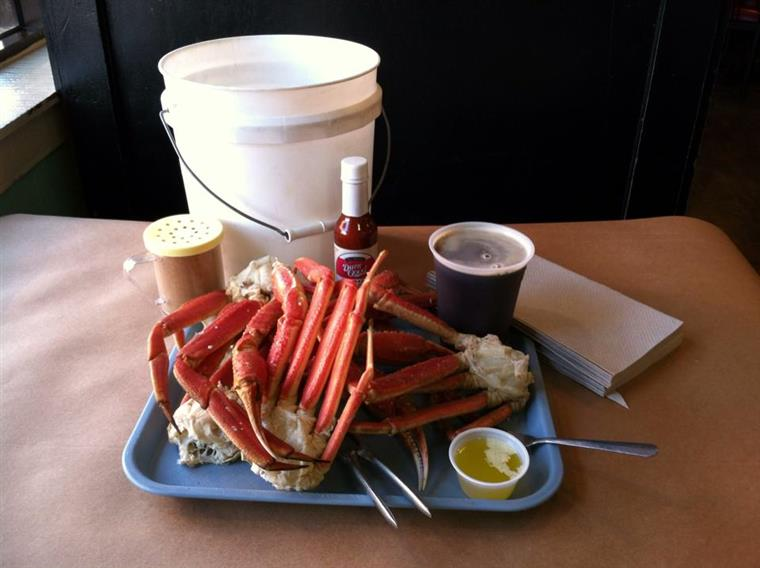 Crab legs with claw crackers and butter on blue tray. Hot sauce, drink, napkins.